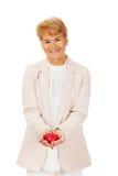 Modello anziano del cuore della tenuta della donna di sorriso Fotografia Stock
