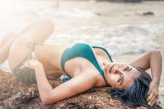 Modello asiatico in bikini che posa trovandosi sulla roccia dal mare sulla spiaggia immagine stock libera da diritti