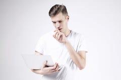 Modello attraente dell'uomo di affari in maglietta bianca isolata sul lavoro bianco con il computer portatile in mano destra Pens Immagine Stock Libera da Diritti