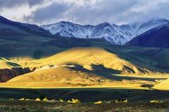 Modello basso della luce del sole sulla collina e sulla montagna innevata Fotografia Stock Libera da Diritti