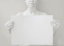 Modello in bianco del manifesto di progettazione La donna ha coperto di pittura bianca che tiene una carta fotografia stock