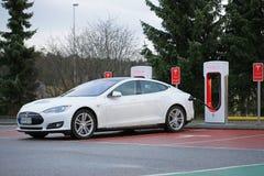 Modello bianco S di Tesla che è fatto pagare alla stazione della sovralimentazione Immagine Stock