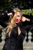 modello biondo che porta cappotto nero e vestito che posano nei raggi di immagine stock