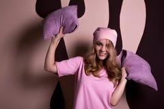 Modello biondo sorridente attraente che gioca con i cuscini su una s rosa Fotografia Stock Libera da Diritti