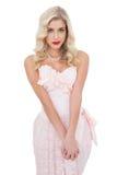 Modello biondo Unsmiling in vestito rosa posando esaminando macchina fotografica immagini stock