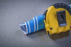 modello blu di Nastro-misura sulla costruzione grigia del fondo concentrata Immagini Stock