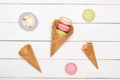 Modello casalingo con i coni della cialda, fondo dei macarons dei dolci Immagini Stock Libere da Diritti