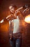 Modello castana alla moda che posa allo studio scuro alla luce mista Immagine Stock
