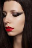 Modello castana con gli orli rossi di lucentezza, il trucco di modo ed i capelli diritti lunghi Immagini Stock Libere da Diritti