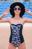 Modello castana di divertimento in un costume da bagno, in un cappello e negli occhiali da sole sul beac fotografie stock