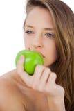 Modello castana premuroso che mangia una mela Immagine Stock