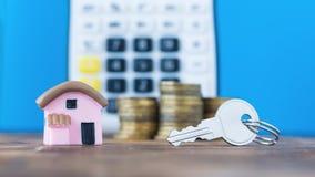 Modello ceramico di una casa con le monete e chiave sui precedenti del calcolatore Immagine Stock Libera da Diritti