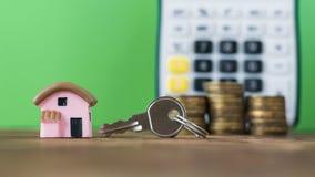 Modello ceramico di una casa rosa con le monete e chiave sui precedenti del calcolatore Immagini Stock
