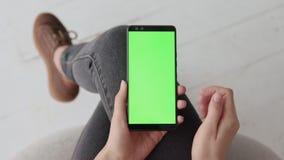 Modello chiave di intensità con lo schermo verde sul telefono cellulare della giovane donna a casa stock footage