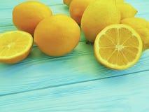 Modello citrico succoso soleggiato delle arance e dei limoni su freschezza di legno blu immagine stock
