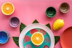 Modello colorato dei piatti e delle tazze decorato dalle foglie esotiche e dai frutti sul copyspace rosa di vista superiore del f Immagine Stock