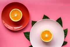 Modello colorato dei piatti e delle tazze decorato dalle foglie esotiche e dai frutti sul copyspace rosa di vista superiore del f Immagini Stock