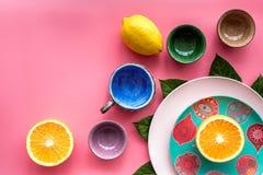 Modello colorato dei piatti e delle tazze decorato dalle foglie esotiche e dai frutti sul copyspace rosa di vista superiore del f Fotografia Stock