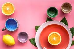 Modello colorato dei piatti e delle tazze decorato dalle foglie esotiche e dai frutti sul copyspace rosa di vista superiore del f Fotografia Stock Libera da Diritti