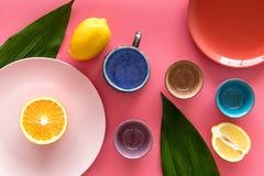 Modello colorato dei piatti e delle tazze decorato dalle foglie esotiche e dai frutti sulla vista superiore del fondo rosa Immagini Stock Libere da Diritti
