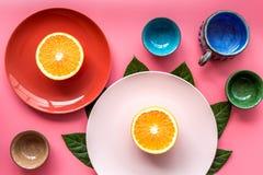 Modello colorato dei piatti e delle tazze decorato dalle foglie esotiche e dai frutti sulla vista superiore del fondo rosa Immagine Stock Libera da Diritti