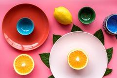 Modello colorato dei piatti e delle tazze decorato dalle foglie esotiche e dai frutti sulla vista superiore del fondo rosa Fotografia Stock