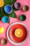 Modello colorato dei piatti e delle tazze decorato dalle foglie esotiche e dai frutti sulla vista superiore del fondo rosa Fotografie Stock Libere da Diritti