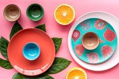 Modello colorato dei piatti e delle tazze decorato dalle foglie esotiche e dai frutti sulla vista superiore del fondo rosa Immagini Stock