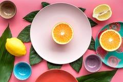 Modello colorato dei piatti e delle tazze decorato dalle foglie esotiche e dai frutti sulla vista superiore del fondo rosa Fotografia Stock Libera da Diritti