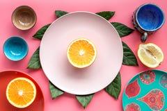Modello colorato dei piatti e delle tazze decorato dalle foglie esotiche e dai frutti sulla vista superiore del fondo rosa Fotografie Stock
