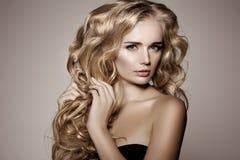 Modello con capelli lunghi biondi Acconciatura dei riccioli delle onde Salone di capelli Fotografie Stock