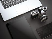 Modello con il computer, la macchina fotografica e la compressa sul pavimento nero Fotografia Stock