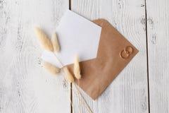 Modello con la cartolina e gli anelli dorati su fondo bianco immagine stock