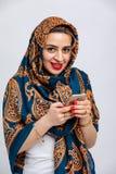 Modello con la sciarpa blu di kalagai sulla testa con i modelli dorati con il telefono in mani isolate su fondo bianco fotografia stock