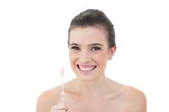 Modello dai capelli marrone naturale contentissimo che tiene uno spazzolino da denti Fotografia Stock