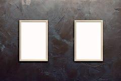 Modello dei manifesti in bianco nei telai di legno sulla parete marrone strutturata dello stucco Fotografia Stock