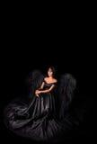 modello del Angelo-diavolo in vestito lungo nero con le ali che si siedono nello studio Fondo nero, dell'interno fotografie stock