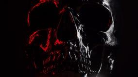Modello del cranio umano dipinto con il nero su fondo scuro con illuminazione rossa variabile Spettrale e sinistro stock footage