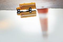 Modello del giocattolo dello scuolabus e riflessione dell'acqua Fotografia Stock
