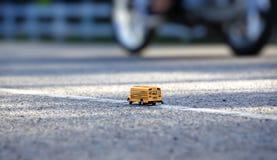 Modello del giocattolo dello scuolabus sulla strada Fotografia Stock Libera da Diritti