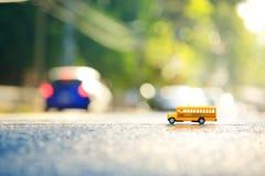 Modello del giocattolo dello scuolabus sulla strada Fotografia Stock