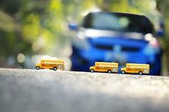 Modello del giocattolo dello scuolabus sulla strada Fotografie Stock Libere da Diritti
