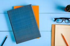 modello del libro di vista superiore e nota della matita sulla tavola di legno blu Fotografia Stock