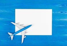 Modello dell'aeroplano e del foglio bianco di carta sui precedenti di legno blu concetto di corsa fotografia stock