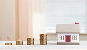 Modello della Camera e pile dorate delle monete Fotografia Stock Libera da Diritti
