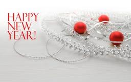 Modello della cartolina d'auguri fatto dei lamé e delle perle d'argento differenti, palle rosse contro fondo di legno con lo spaz Fotografia Stock Libera da Diritti