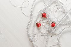Modello della cartolina d'auguri fatto dei lamé e delle perle d'argento differenti, palle rosse contro fondo di legno con lo spaz Fotografia Stock