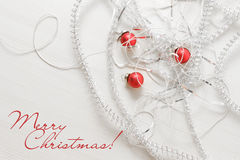 Modello della cartolina d'auguri fatto dei lamé e delle perle d'argento differenti, palle rosse contro fondo di legno con lo spaz Fotografie Stock Libere da Diritti