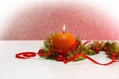Modello della cartolina d'auguri fatto di lamé giallo e verde con le palle rosse e dorate di natale, candela rossa dell'arancia d Fotografia Stock