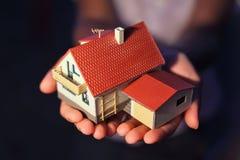 Modello della casa con il garage sulle mani Fotografia Stock Libera da Diritti